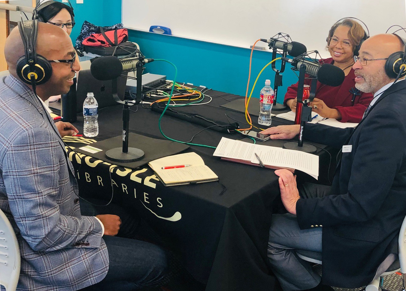 Rodney Clark (left) speaks with Check It Out! podcast host Ken Harvey (right) and special co-host Lynne Varner (second from right) about technology and the Internet of Things.